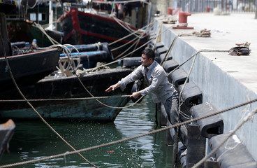 A fisherman anchors a boat at a fish harbour as Typhoon Mangkhut approaches Shenzhen