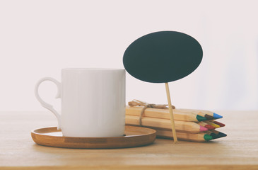 coffee cup next to empty blackboard sign on wooden table.