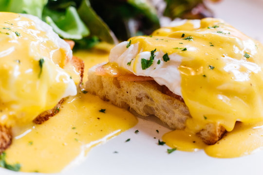 Close up Egg benedict served with salad in white plate on wooden table for delicious breakfast and brunch.