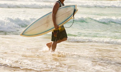 Man surfer with surfboard, man carrying his surfing board walking on the beach at sunset