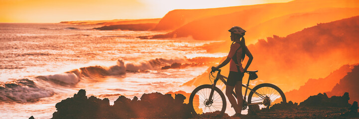 Sport biking cyclist looking at ocean beach coastline during cycling trail race trip. Silhouette of woman athlete training mountain bike outdoors at sunset, banner panorama.