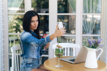 A beautiful brunette has a European appearance, dark straight hair, makes selfie on her smartphone, drinks a delicious minty cocktail, works on a laptop. Freelancer, gadgets, technology.