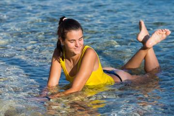Girl in yellow tank top lying in sea water