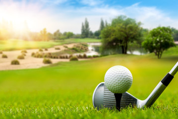 White Golf ball on tee ready to be shot on blurred beautiful landscape of golf course in bright day time with copy space. Sport, Recreation, Relax in holiday concept.