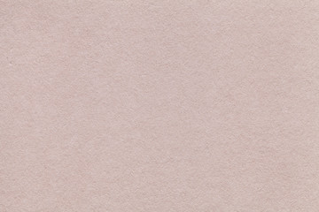 Texture of old beige paper closeup. Structure of a dense cardboard sand color. The background