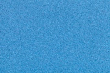 Texture of old blue paper closeup. Structure of a dense cardboard. The azure background.