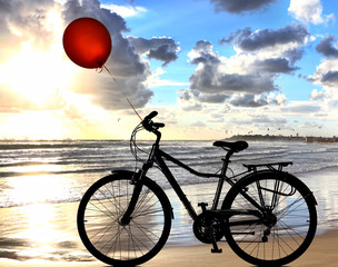 Bike lonely is on wet sea sand of the beach against the backdrop of beautiful seaside at sunset. Red balloon is flying up. Leisure and sport. Adventure and dreams