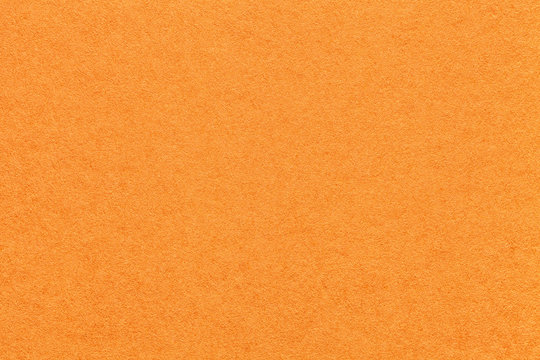 Texture of old bright orange paper background, closeup. Structure of dense carrot cardboard