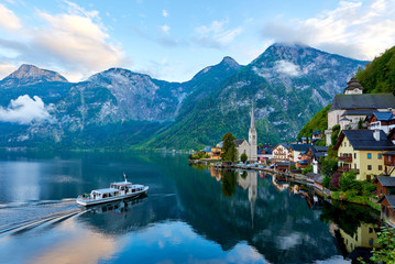 Foto op Plexiglas Kust Scenic picture-postcard view of famous Hallstatt mountain village with Hallstatter lake and boat in Austrian Alps. Autumn sunset on Hallstatt lake with beautiful clouds.