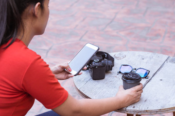 Young girl are playing internet on mobile phones and have a camera, sunglasses, a coffee cup is on a wood table.