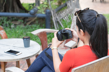 Women are playing camera and have a mobile phone, a coffee cup is on a wood table.