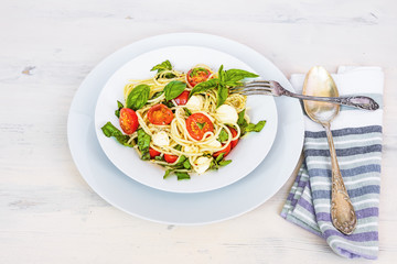 Italian food - Spaghetti caprese in a plate on a light rustic background, top view. Pasta with mozzarella, cherry tomatoes and basil