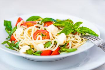 Spaghetti caprese - traditional Italian pasta with mozzarella cheese, cherry tomatoes and basil