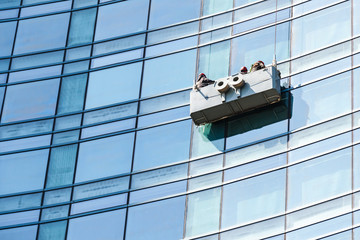 Blue glass facade cleaning with cradle