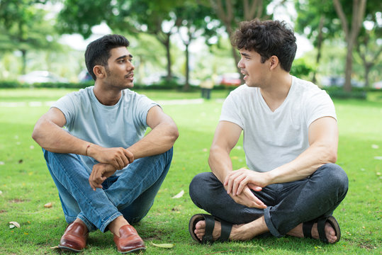Confident young friends discussing last news while spending time in park. Serious students sitting on grass and chatting. Weekend concept