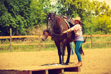Cowgirl getting horse ready for ride on countryside