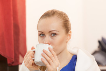 Woman lying on sofa under blanket drinking tea