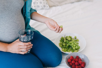 Cropped photo of young pregnant woman with glass of water eating fruits in bed