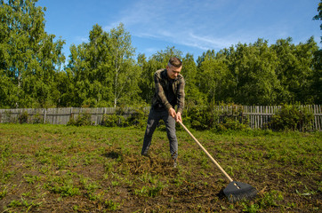 A young gardener in the garden removes the beveled grass with a rake on a wooden fence and forest background.