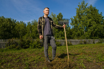 A young guy is standing in the garden with a rake on a wooden fence background.