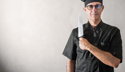 cuoco in divisa nera e lungo coltello