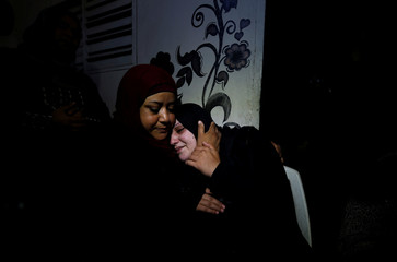 Mother of 11-year-old Palestinian boy Shadi Abdel-Al, who was killed during a protest at the Israel-Gaza border fence, is comforted as she mourns during his funeral in the northern Gaza Strip