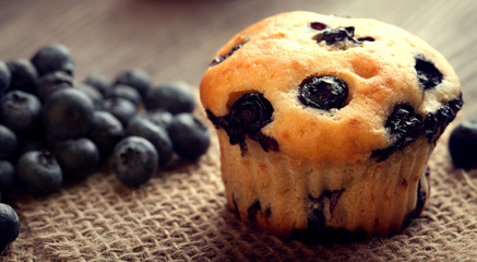 muffin with blueberries on a wooden table. fresh berries and sweet pastries on the board.