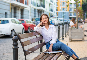 Young beautiful smiling female with a laptop sits on a bench in the business part of the city.