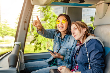 Two girls travel by bus in Europe, public transport, trip and vacation and friendship concept