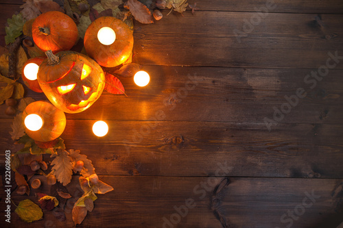 concept of Hallowen, autumn still life of small pumpkins that lie on dry leaves on a dark wooden background at the upper left border of the frame with burning candles laid out on the same pumpkins.