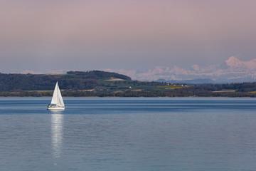White boat sailing on Neuchâtel Lake in Switzerland