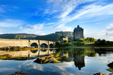 Tourists favourite place in Scotland - Isle of Skye. Very famous castle in Scotland called Eilean Donan castle.  Top of the mountains.Scottish Highlands. Castle with reflection in the lake.