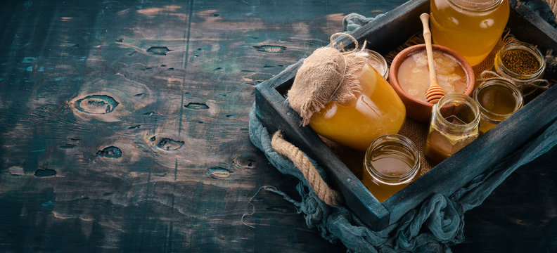 Set honey in a wooden box on a wooden background. Free space for text. Top view.