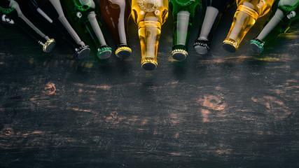A large selection of beer bottles. On a black wooden table. Free space for text. Top view.