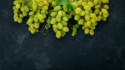 Green grapes with leaves of grapes on a stone table. Top view. Free space for text. Fototapete