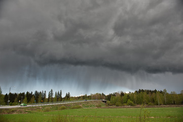 Stormy rain clouds over rural landscape in Finland.