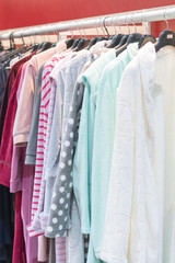 many bathrobes any colors. Racks and hangers with cotton and bamboo dressing gowns. Dressing gowns on the hanger in the store. vertical photo.