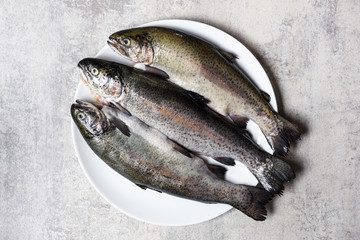 Three trout fish on white plate closeup. Food photography