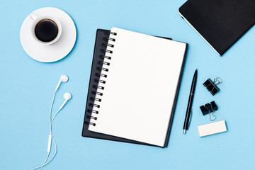 Top view workspace mockup on blue background with blank notepad, pen, coffee cup, lipstick, headphones and supplies. Note pad space for text input.