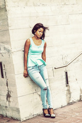 Unhappy African American Woman wearing light green tank top, drop earrings, blue distressed jeans, wedge pumps, standing against wall outside in New York, looking down, sad, thinking, lost in thought.