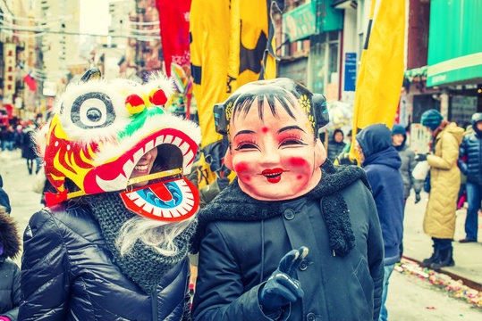 Two people wearing traditional Chinese masks, big head doll and lion, walking on street in Chinatown, downtown of Manhattan, New York City, celebrating Chinese New Year. Many people on background.
