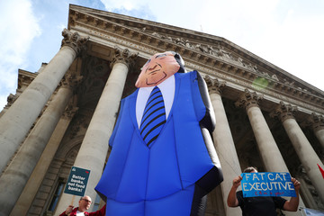 Protesters hold up placards and a giant inflatable man in a suit and tie outside the Royal Exchange, opposite the Bank of England, before a speech by the Labour Party's shadow Chancellor of the Exchequer, John McDonnell, in London