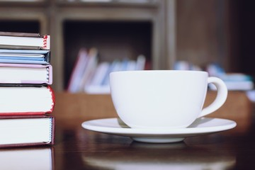 cup coffee on table in cafe. background style library book shelf. note pad. education