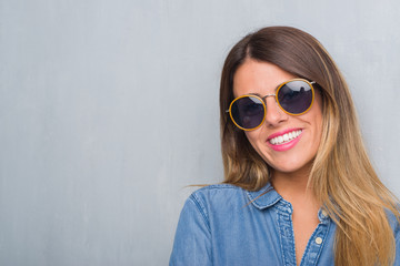 Young adult woman over grunge grey wall wearing retro sunglasses with a happy and cool smile on face. Lucky person.
