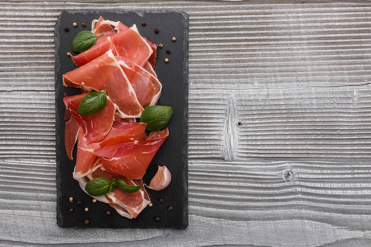 Italian prosciutto crudo or spanish jamon on a stone plate wooden background
