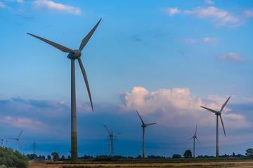 windmills on green at sundown