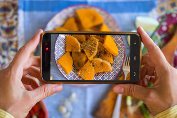 Woman hands takes photography of food on table with phone. Dinner, lunch. Baked, cooked pumpkin slices. Smartphone photo for social networks or blogging post. Vegetarian, healthy, organic