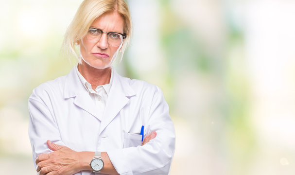 Middle age blonde therapist woman wearing white coat over isolated background skeptic and nervous, disapproving expression on face with crossed arms. Negative person.
