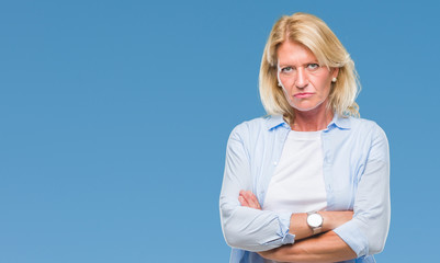 Middle age blonde woman over isolated background skeptic and nervous, disapproving expression on face with crossed arms. Negative person.