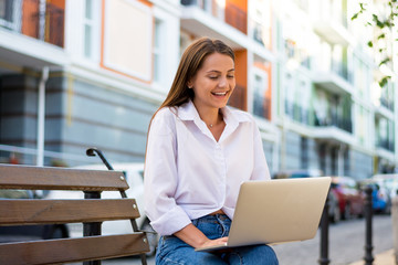 Young beautiful laughing female with a laptop sits on a bench in the business part of the city.